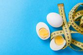 Egg diet for weight loss. Cleaning the body of toxins. Full healthy breakfast. Egg cut in half with protein and yolk and measuring tape. Blue background. Copy space for text poster