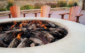 Adirondack chairs by the fire pit with flames
