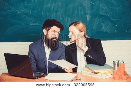 School education. Take into account educational norms. Prepare for school lesson. Teacher and supervisor working in school classroom. School educator with laptop and principal with official documents poster