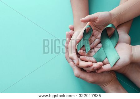 Adult And Children Hands Holding Teal Ribbons On Blue Background, Ovarian Cancer, Cervical Cancer, A
