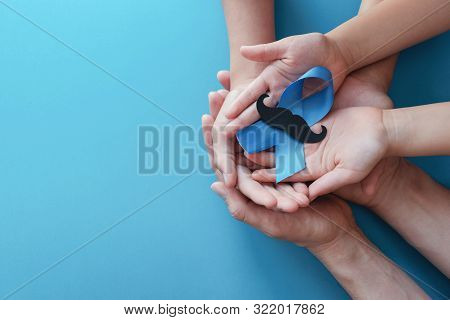 Family Hands Holding Light Blue Ribbonwith Mustache On Blue Background , Prostate Cancer Awareness,