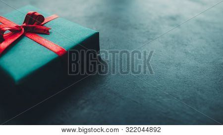 Birthday Present. Cropped Closeup Of Gift Box With Red Ribbon Bow On Dark Teal Blue Background. Copy