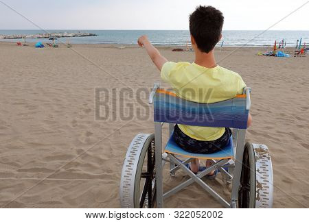 Young Boy With Yellow T-shirt On The Wheelchair With Big Wheels To Move On The Sandy Beach
