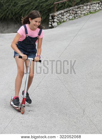 Fast Little Girl On Scooter With Dungarees Jeans In Summer