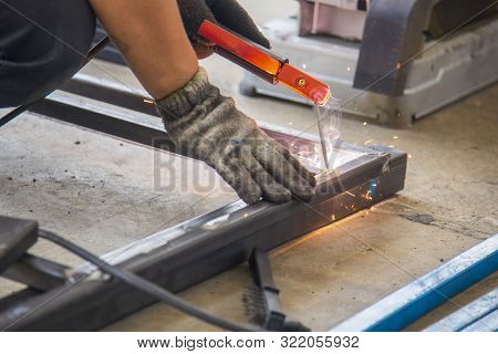 The Skill Worker Use The Electric Welding Machine Welding The Metal Tube Structure For Assembly  The