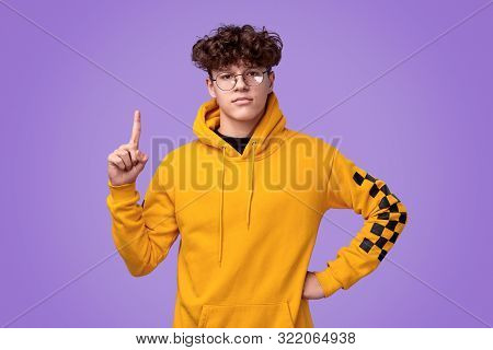 Confident Youngster In Bright Yellow Hoodie And Round Glasses Pointing Up And Looking At Camera Whil