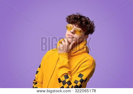 Trendy Youngster In Yellow Hoodie And Sunglasses Rubbing Chin And Looking Away Against Purple Backgr