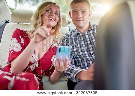 Photo Of Happy Women And Men With Phone In Hands Sitting In Back Seat Of Car During Day . Sunflare E