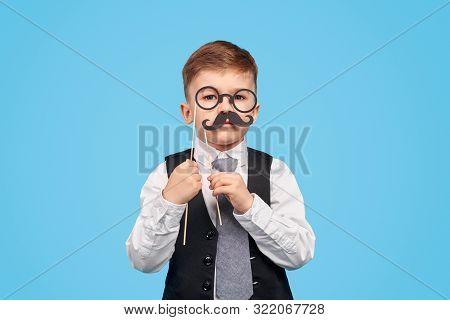 Cute little boy in suit wearing paper glasses and moustache while pretending to be gentleman against blue background poster