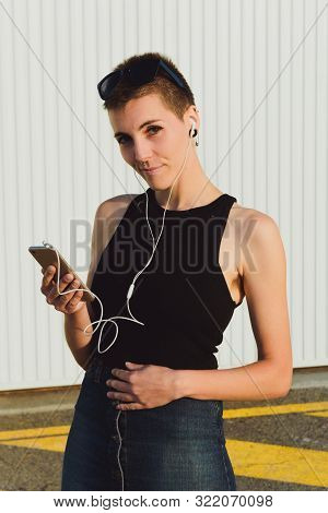 Attractive Woman With Underarm Hair Listens To Music With Headphones On Her Smartphone. She Is In Fr