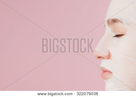 Beautiful Young Woman Is Applying A Cosmetic Tissue Mask On A Face On A Pink Background. Healthcare