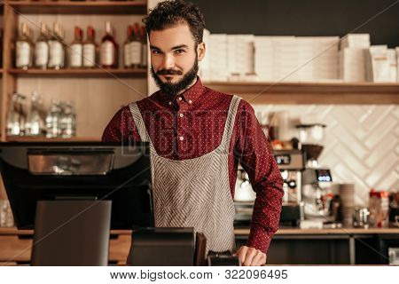 Handsome Bearded Man In Apron Looking At Camera While Standing Near Cash Register Behind Counter In