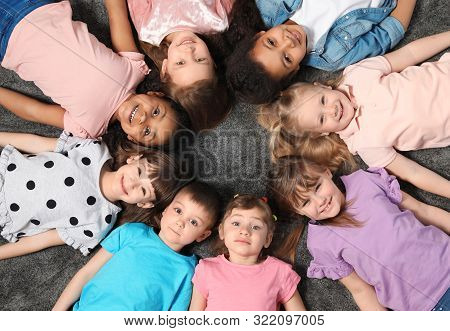 Adorable Little Children Lying On Floor Together Indoors, Top View. Kindergarten Playtime Activities