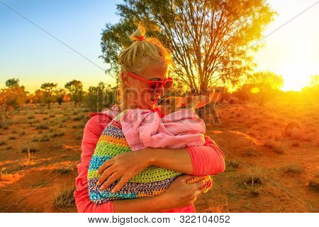 Tourist woman holding ed kissing kangaroo joey at sunset light in Australian outback. Interacting with cute kangaroo orphan. Australian Marsupial in Northern Territory, Central Australia or Red Center poster