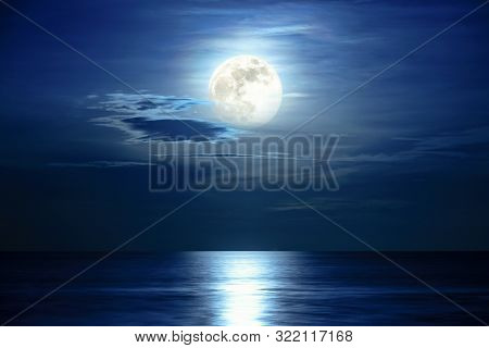 Super Full Moon And Cloud In The Blue Sky Above The Ocean Horizon At Midnight, Moonlight Reflect The