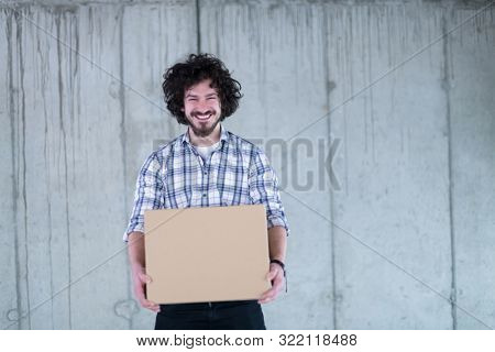 young successful smiling casual businessman carrying cardboard box in front of a concrete wall during moving in at new startup office