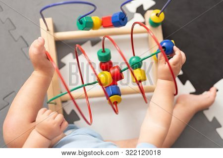 Baby Playing With Educational Toy In Nursery. Learning Colorful Wooden Toy.developing Toy. The Labyr
