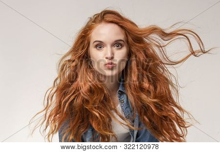 Redhead Girl Sending Air Kiss to Camera, Pouting Lips Over Light Studio Background poster