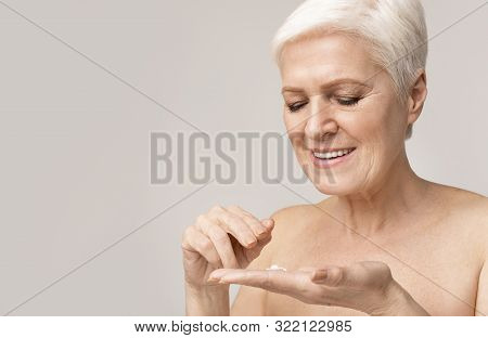 Happy Senior Woman Applying Anti-wrinkle Cream For Skin, Light Backgroung With Free Space