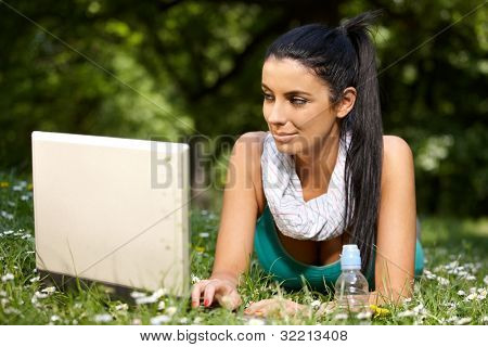 Pretty girl laying in grass in citypark, browsing internet, looking at screen.