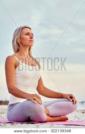 Middle-aged Woman Wearing Activewear Seated On Mat In Lotus Position Do Meditation On Nature Feel Ca
