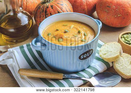 Homemade Pumpkin Soup And Pumpkins On Beige Rustic Background. Seasonal Autumn Food - Spicy Pumpkin
