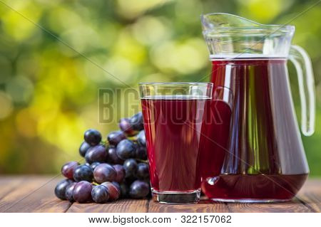 Fresh Grape Juice In Glass And Jug With Ripe Bunch Of Dark Blue Berries On Wooden Table Outdoors