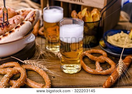 Fresh Craft Beer. German Sausages On The Grill. Traditional German Sausages And Pastry Brezel For A