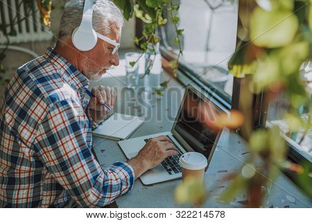 Man Listening To Music And Working On Laptop Stock Photo