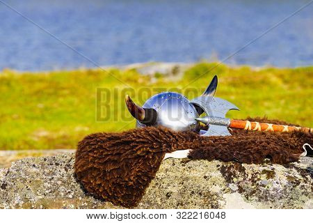 Equipment Of Viking Or Barbarian Warrior Outdoor On Nature. Viking Helmet With Axe On Brown Fur Of T