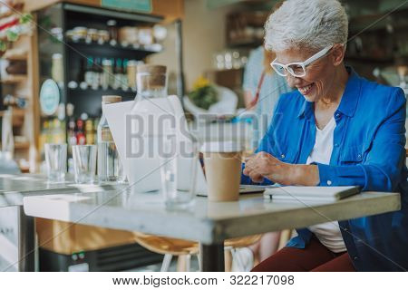 Mirthful Lady Laughing While Working Stock Photo