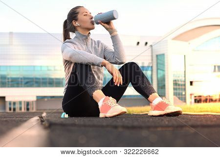 Beautiful Young Woman In Sports Clothing Drinking Water After Sport Exercise Outdoors In Stadium