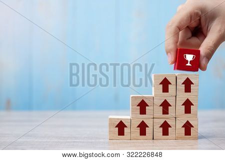 Businessman Hand Placing Or Pulling Red Block With Trophy And Growth Up Arrow On Table Background. B