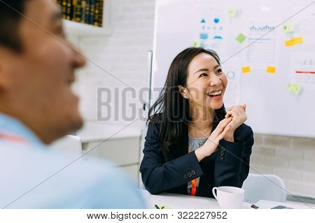 Asian Mature Business Woman Smiling And Looking At Other Business People While Sitting In Meeting. S