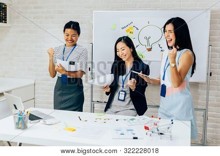Smiling Asian Young And Mature Business Women Standing In Line With Arms Raised Up Gesture In Meetin