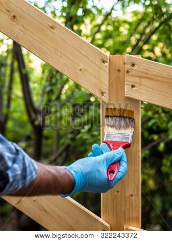Adult Craftsman Carpenter With The Brush Painting The Boards Of A Wooden Fence. Housework, Do It You