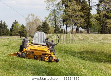 No person on expansive lawn with a yellow zero-turn mower poster