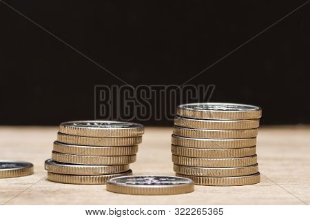 Many Euro Coins Stacked On Black Background.