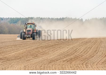 Farmer In Tractor Preparing Land With Seedbed Cultivator As Part Of Pre Seeding Activities In Early