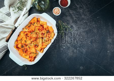 Raw Pumpkin Sliced In Small Pieces With Thyme In A Baking Dish On A Wooden Background.