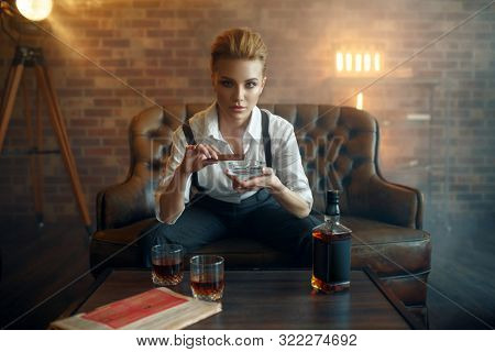 Woman in strict clothes smoking cigar, gangster