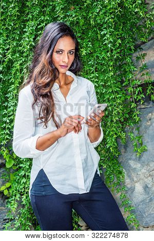 poster of Young Beautiful East Indian American Woman with long hair traveling in New York City, wearing white long sleeve shirt, standing by rocks with long green leaves at Central Park, texting on cell phone.