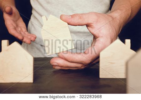 Toy House In Man Hand. Real Estate Concept With Wooden Toy Home.