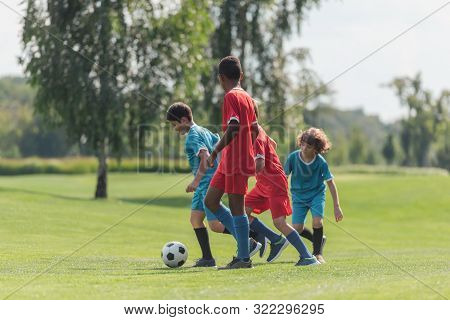 Cute Kids Playing Football With African American Friend