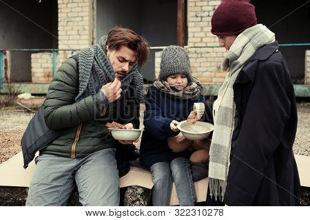 Poor Young Family With Bread On Dirty Street