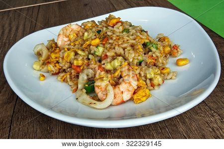 Rice With Mixed Seafood And Eggs In Bowl Plate On A Wooden Table. Asian Traditional Food: Yaki Meish