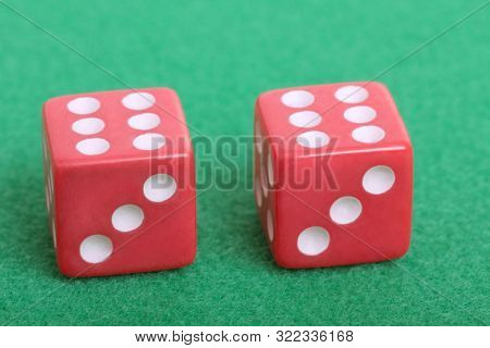 Red dice on a table with green cloth