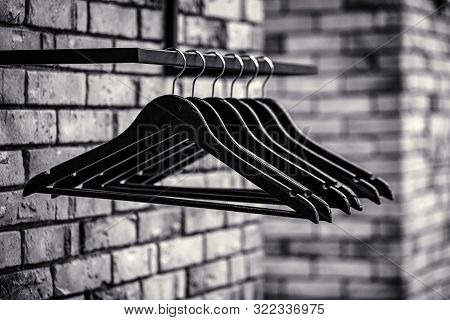 Many Wooden Black Hangers On A Rod. Store Concept, Sale, Design, Empty Hangers. Black Friday. Black