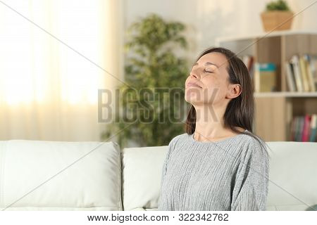 Relaxed Woman Breathing Fresh Air Sitting On A Couch In The Living Room At Home