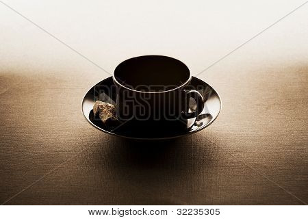 Black coffee cup with saucer on gradient background